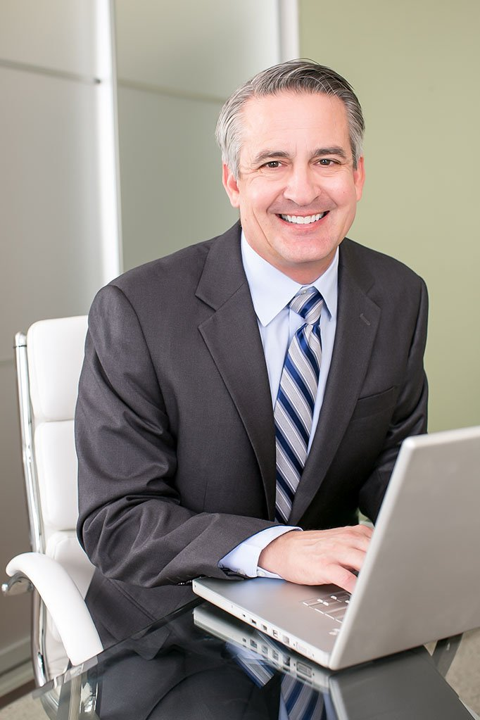 Man siting at a desk smiling on his computer, clearinghouse services, FMSCA drug testing