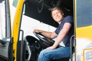 CDL Driver in his truck smiling, clearinghouse services, FMSCA drug testing